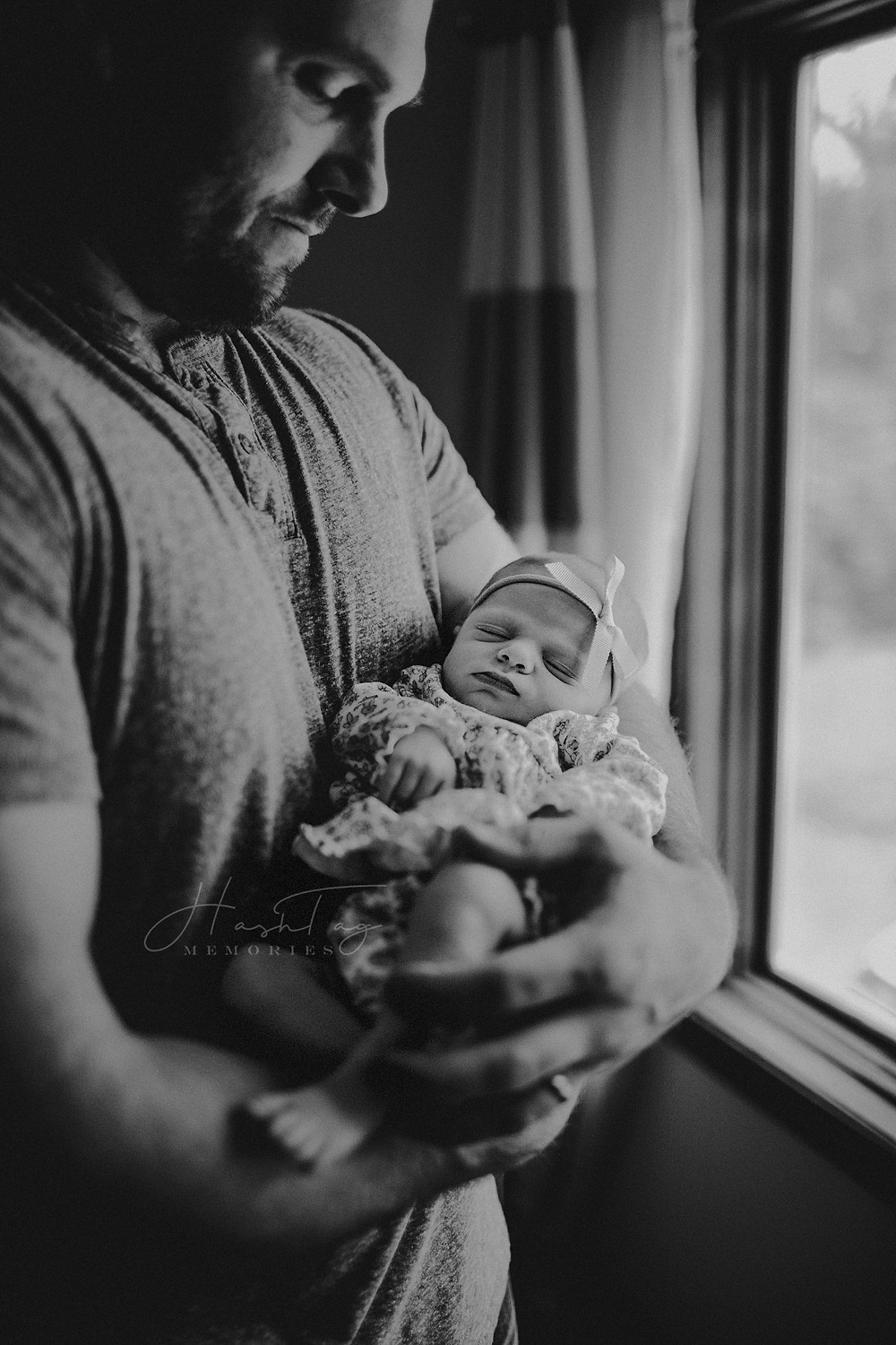 daddy holding newborn girl in pink bow, moody photography, newborn photographer