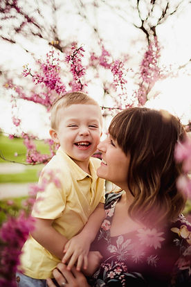 toddler and mother snuggle during spring family photo session at coxhall gardens by noblesville photograher