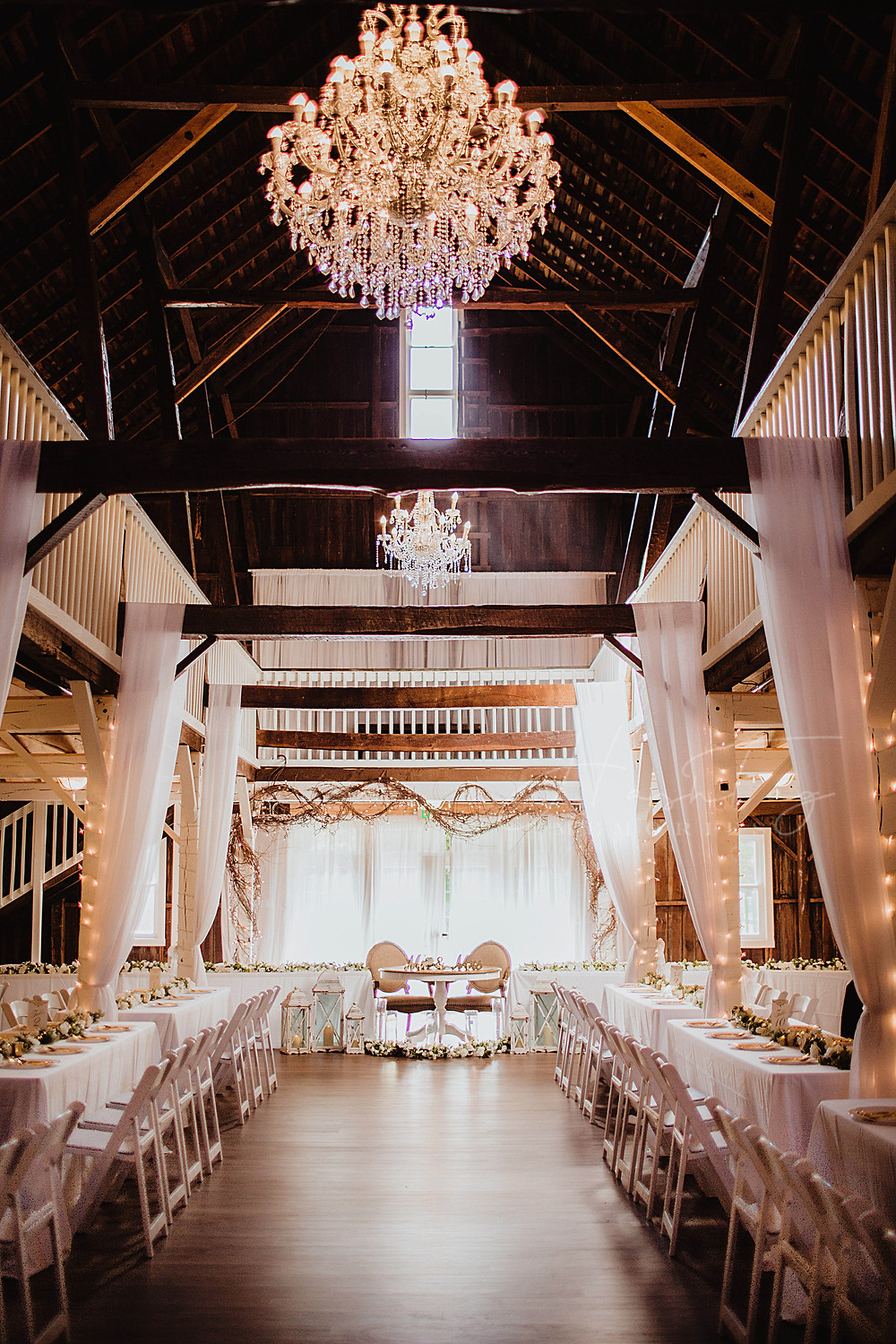 classy barn wedding venue in indiana for midwest brides with big crystal chandeliers
