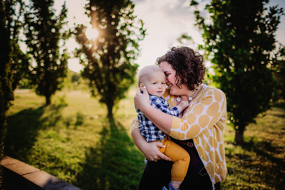 baby boy in navy and yellow held by mom during family photos