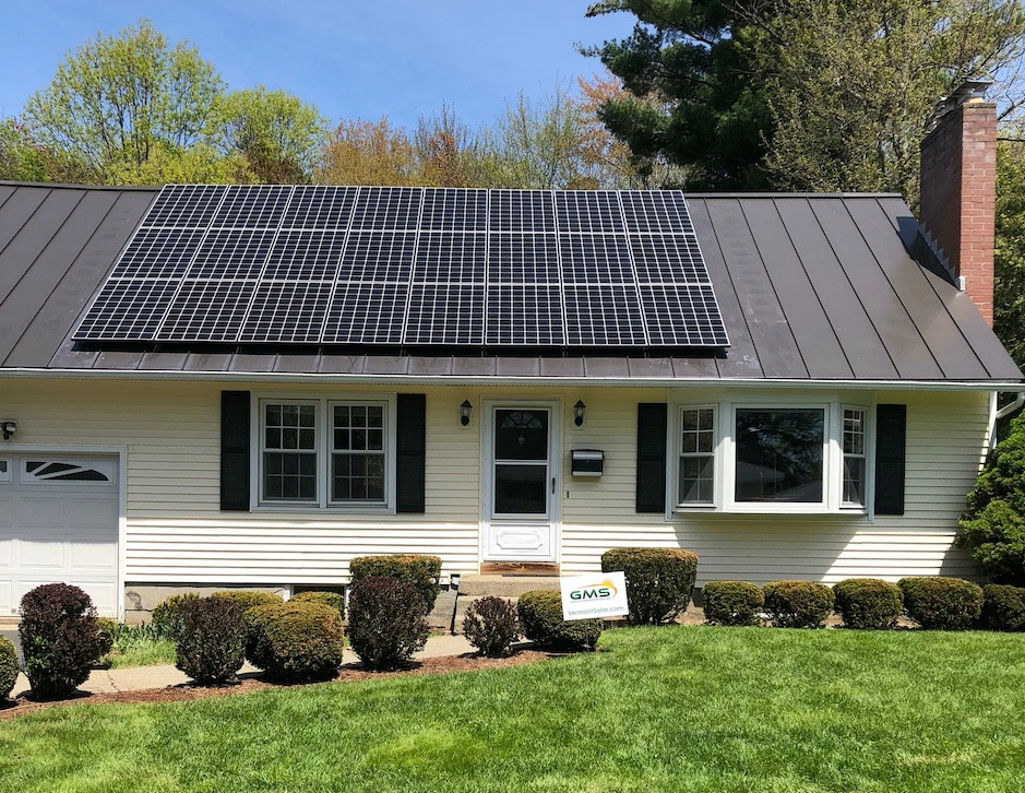 Yellow house with solar panels installed by Green Mountain Solar