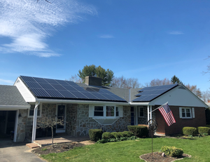 Solar panels on a roof with a blue sky and American flag, installed by Granite State Solar