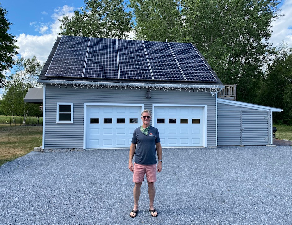 Vermont man standing in front of garage with solar panels
