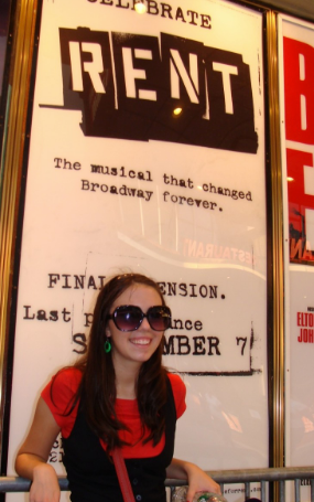 Girl stands in front of poster declaring RENT's final performance on Broadway.