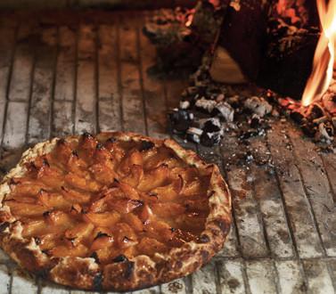 A baked pie near an open fire