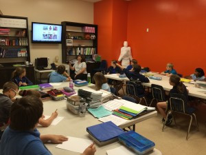 The fifth grade class debates what animal they'll purchase next through World Vision.