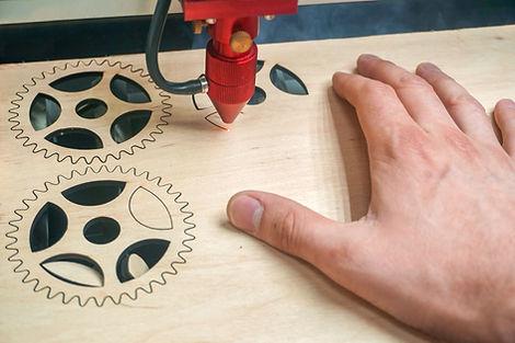 Laser cutting machine in process. Worker