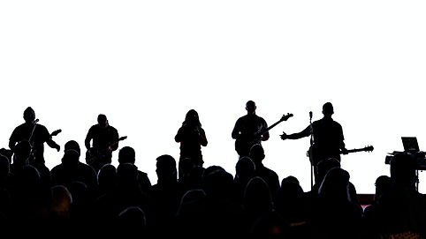 A band on stage, in silhouette. There are a number of people in the crowd