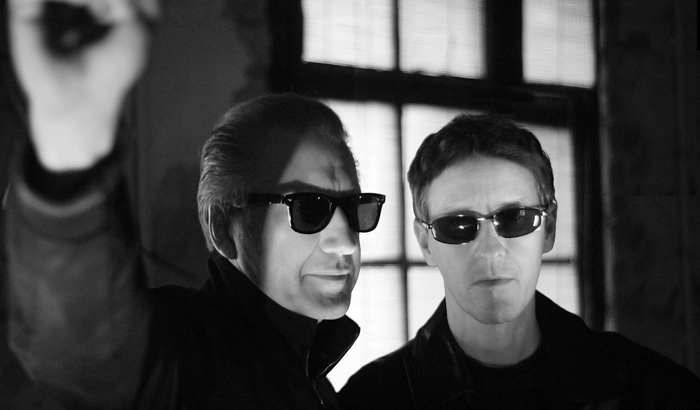 A black and white image of the band The Venus Fly Trap/ Both men are wearing sunglasses and are standing in front of a dimly lit window