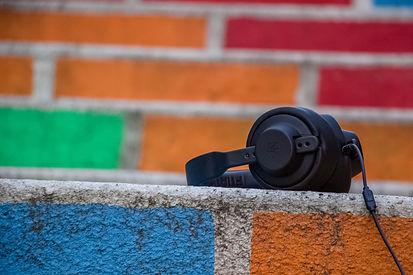 headphones on a multi-coloured brick backgroud.