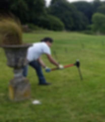 A man with a sledgehammer driving marquee stakes into grass