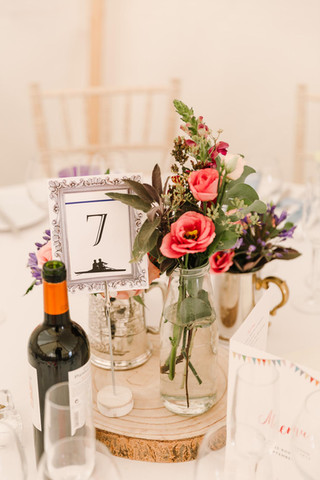 Log slice centrepiece with flowers in glass jars