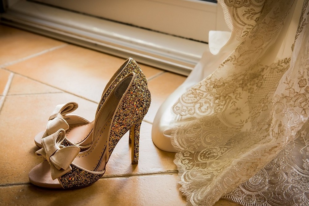 Sparking gold wedding shoes near dress