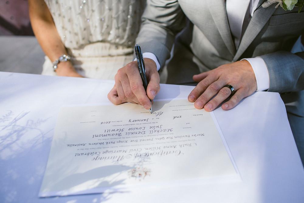 Bride & groom (hands) signing wedding certificate