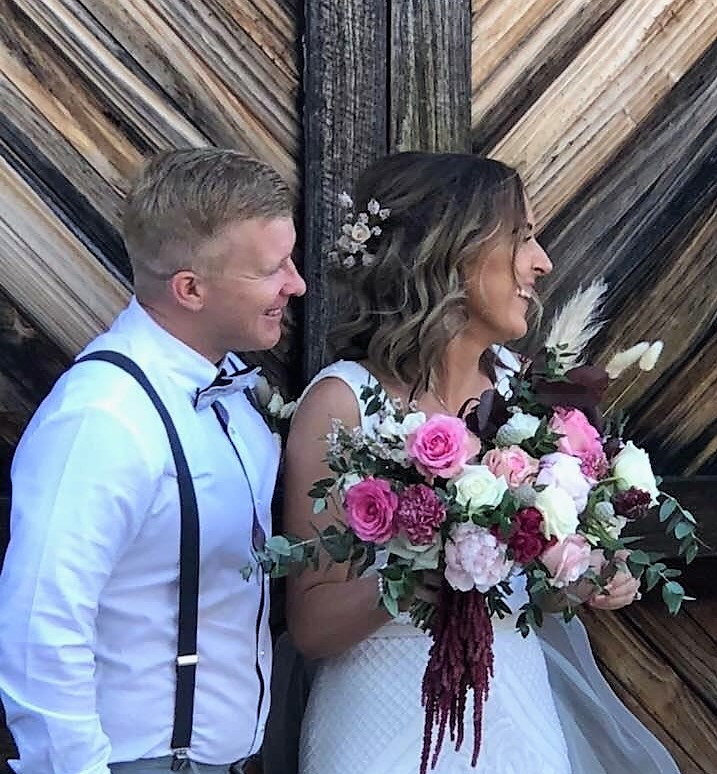Groom with Bride holding flowers in front of door
