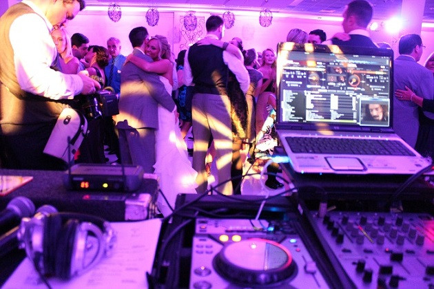 DJ equipment on table and people dancing