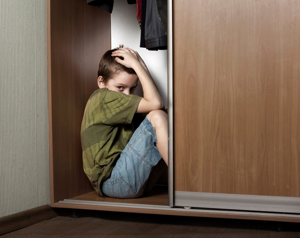 Boy hiding from painful childhood