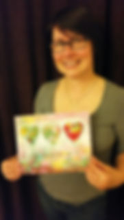 """Leeanne proudly holding her """"You are loved"""" artwork"""