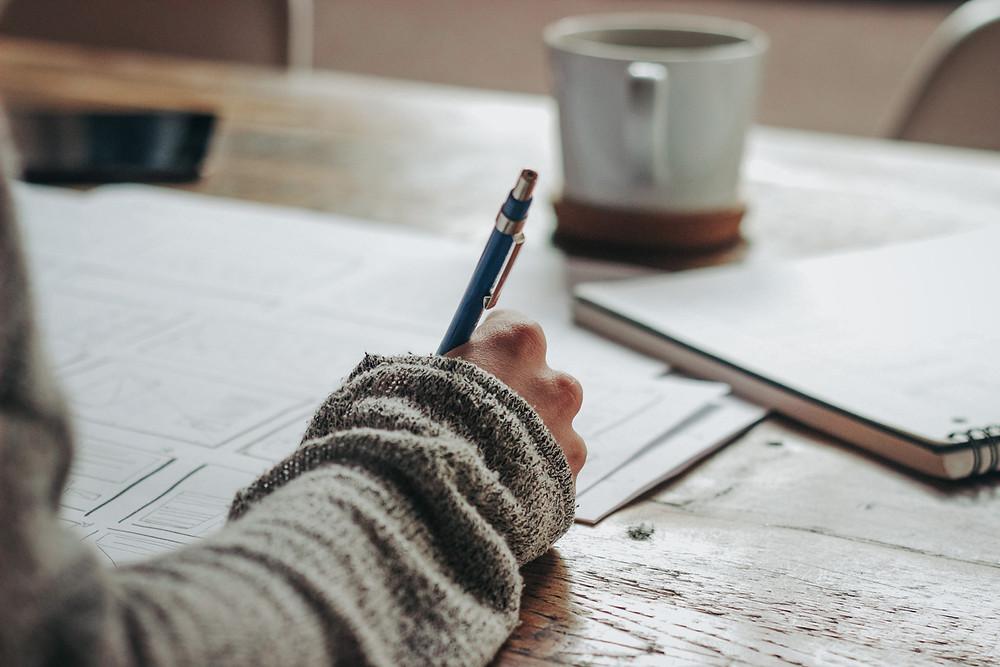 Person schreibt an einem Plan mit einer Tasse Kaffee vor sich.