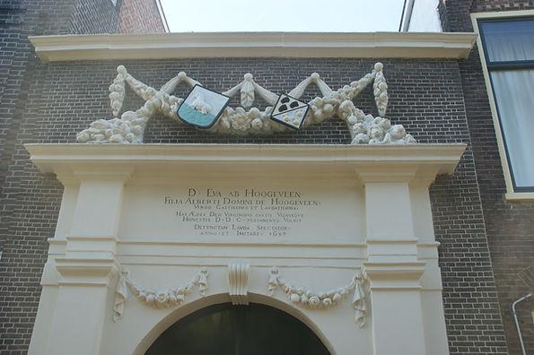 Vertaling van het opschrift: Vrouwe Eva van Hoogeveen, dochter van Albertus, Heer van Hoogeveen, een zeer kuise en lofwaardige Maagd, heeft deze gebouwen ter ere van God aan kuise Maagden en eerbare Weduwen in 1650 bij testament beschikt. Loof de overledene, toeschouwer en volg haar na. Anno 1659