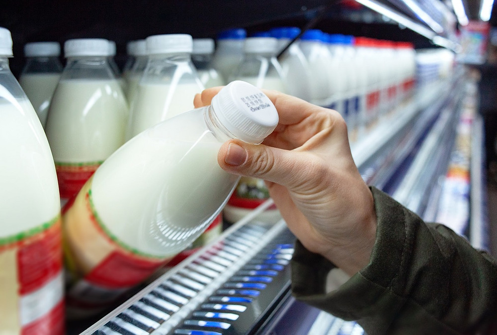 Womans hand holding milk bottle in supermarket