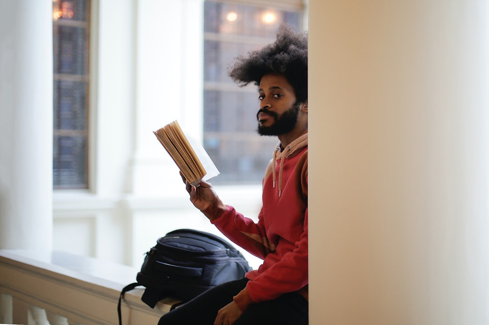 Man Reading a Book while Waiting For His Next Class