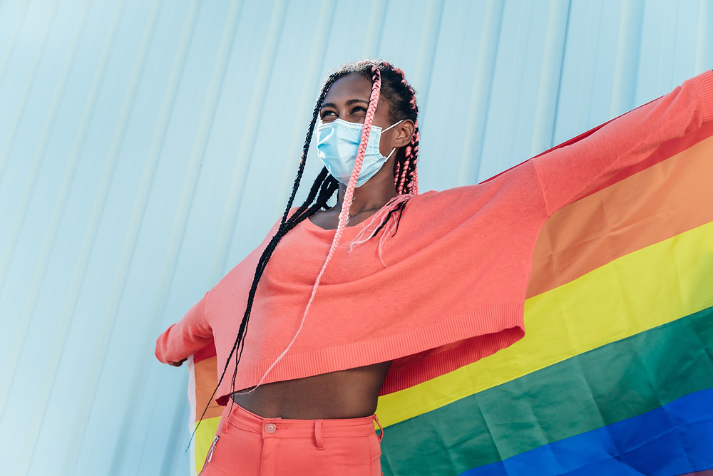 Young black woman with face mask holding a gay pride rainbow flag