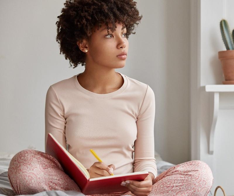 dark skinned woman sits crossed legs,makes notes in diary