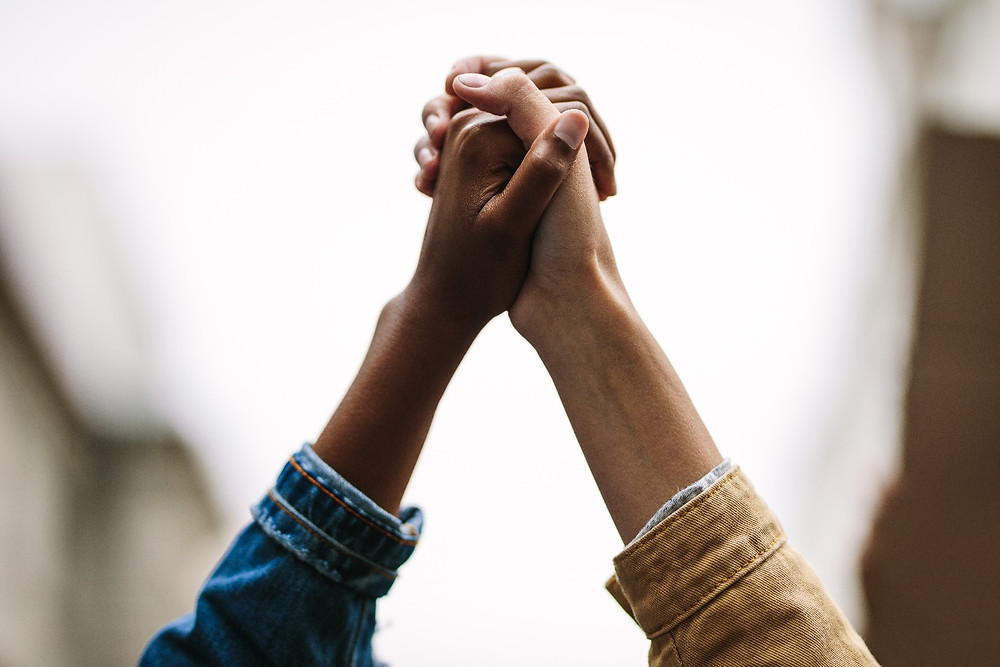 Symbol of unity. Two women activists holding hands.