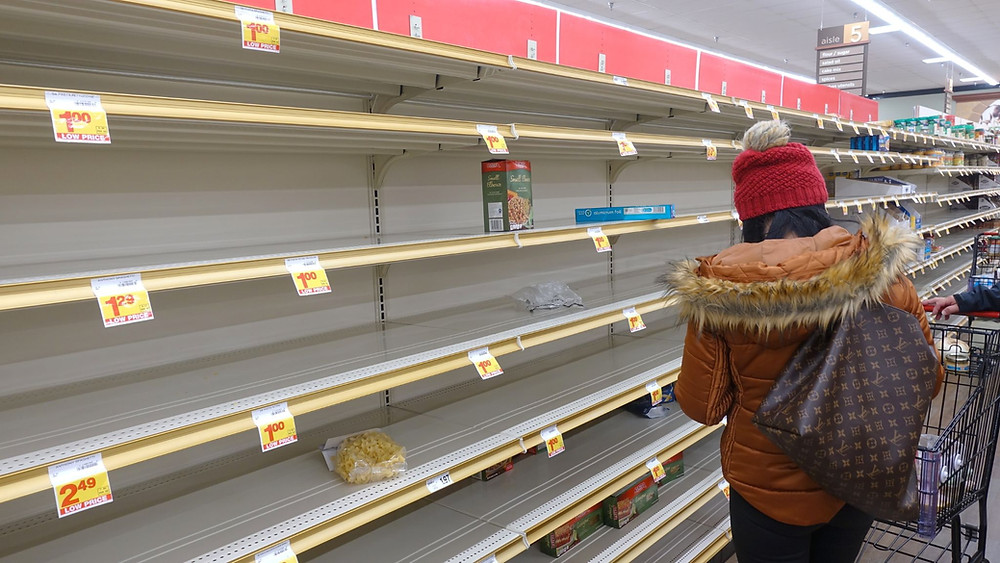 A shopper in front of empty shelves in a grocery store