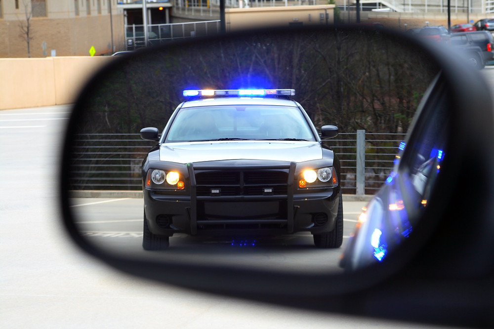 View on side mirror of a Police car with lights