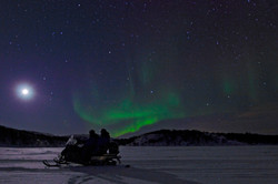 Snowmobile and aurora on the tundra