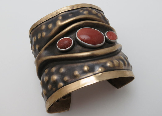 Synclastic embossed and folded cuff