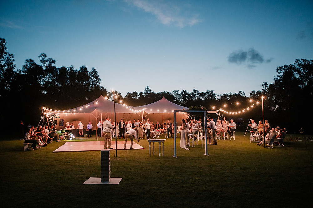 The best man of a Yamba wedding at the Rivershack is doing his speech in front of the wedding crowd. Guests are standing under a willow tree marquee and the area is lit up with festoon lighting.