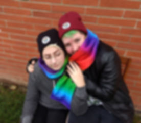 Two LGBT cuties are wrapped up in a rainbow gradient fleece scarf and wearing Queerest Gear logo bea