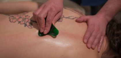 A massage therapist uses a scraping tool to release muscle tension