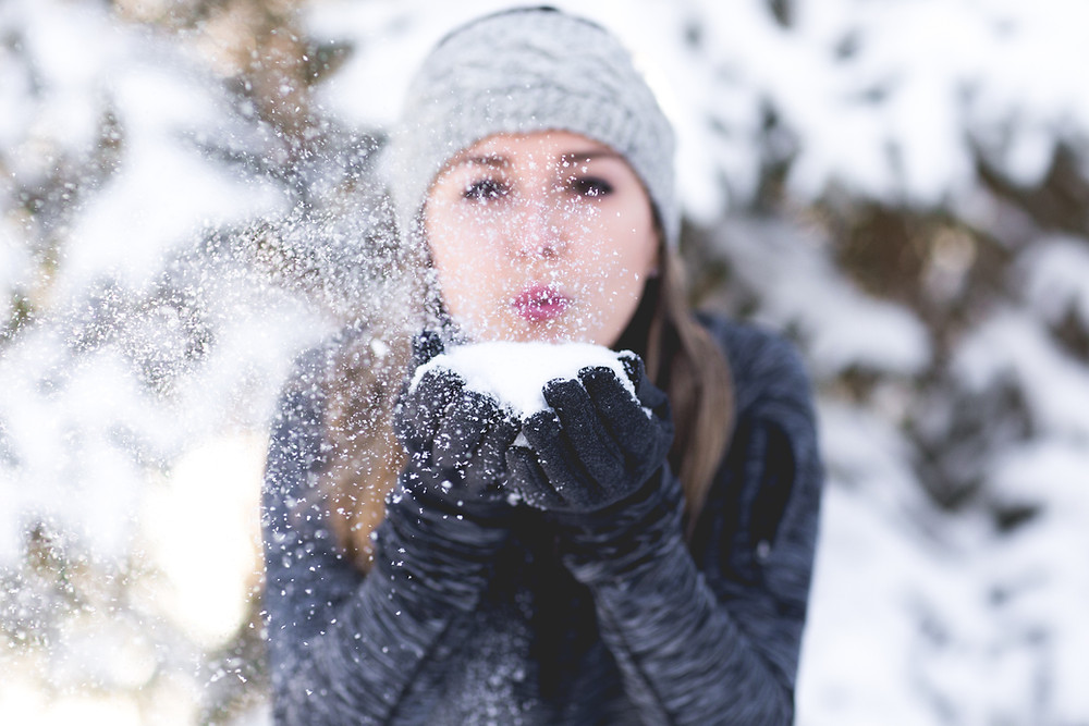 A woman playfully blows snow out of her hands outside