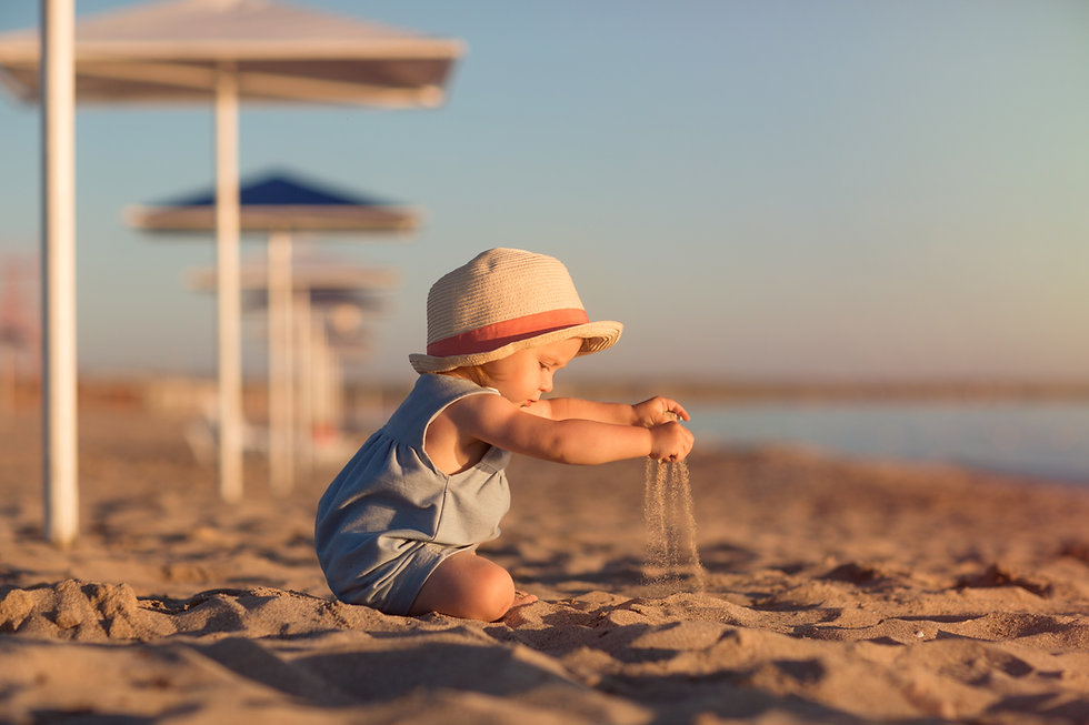 kid in a hat playing with sand on the be