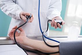 checking blood pressure during DOT examination
