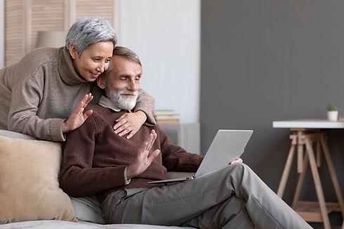 adorable-senior-couple-video-conferencin