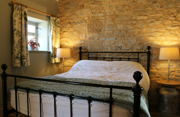 Bedroom with feature stonework and original beams.