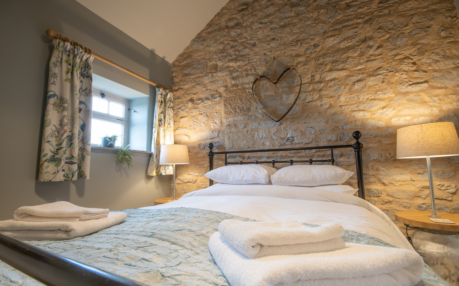 Bedroom with feature stone walls and original beams