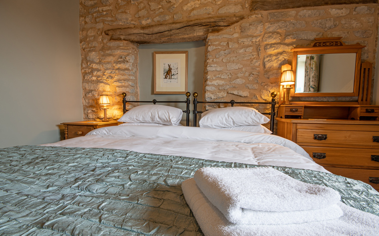 Master bedroom with feature stone walls and original beams