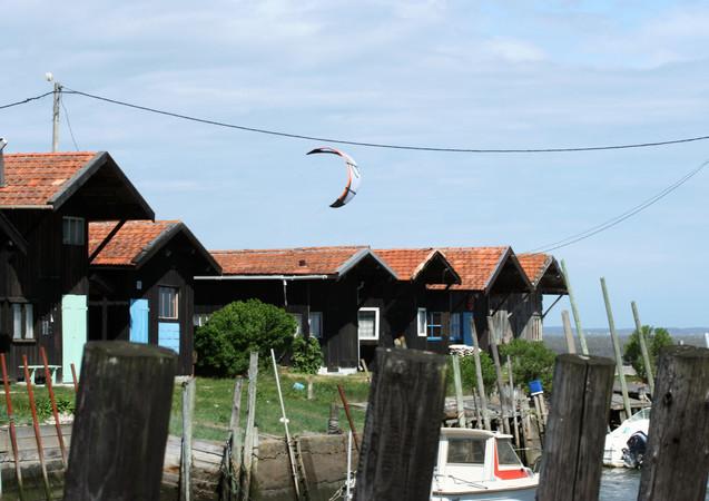 Une voile au dessus des cabanes ostréïcole, Gujan-Mestras