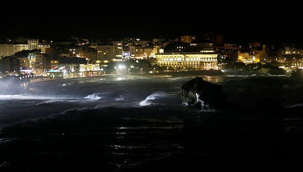 un projecteur éclaire l'océan en tempête, Biarritz de nuit