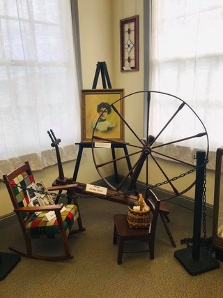 Spinning Wheel  form the family of Pat Heddon. It belonged to his grandmother and is accompanied by her rocker, her portrait a childs chair. Wool samples on loan from our spinners!