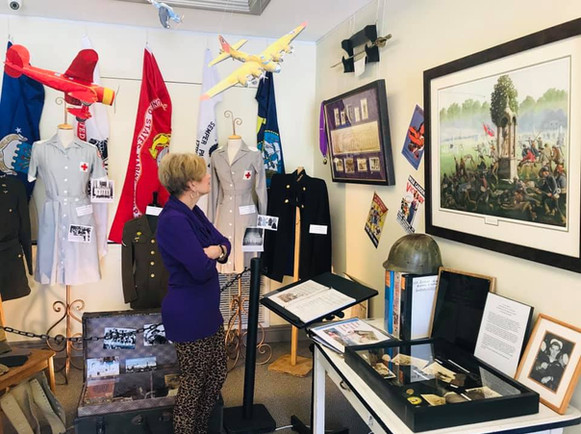 Pat Genre is admiring the Purple Heart on display from the family of David Iles.  To her right are atifacts and information from the Family of Clyde Meyers.
