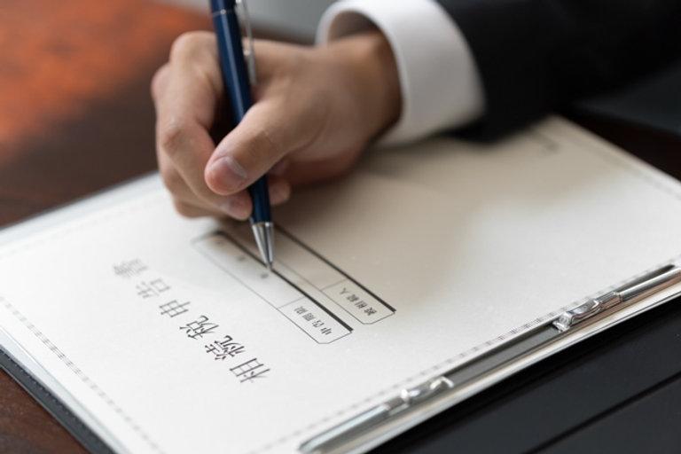 相続税申告書に記入する男性の手