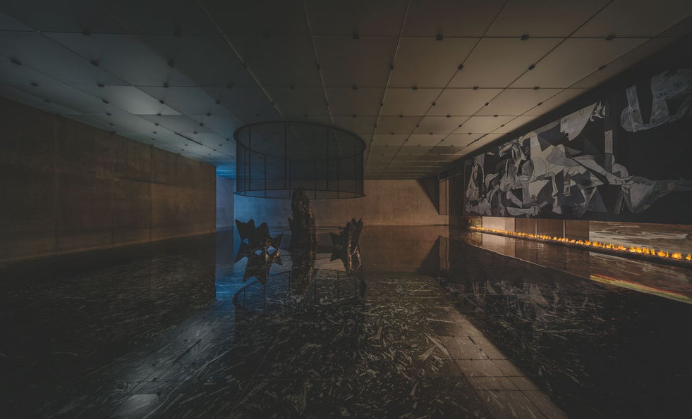 """Carreaux de carrelage en marbre noir avec incrustations de fossiles d'orthoceras, reproduction peinte à la main de """"Guernica"""" de Pablo Picasso, de """"Giraffatitan brancai at the Mudbaths"""" de John Conway et de """"Cro-Magnon Man"""" de Zdeněk Burian, feu venant d'un système à gaz."""