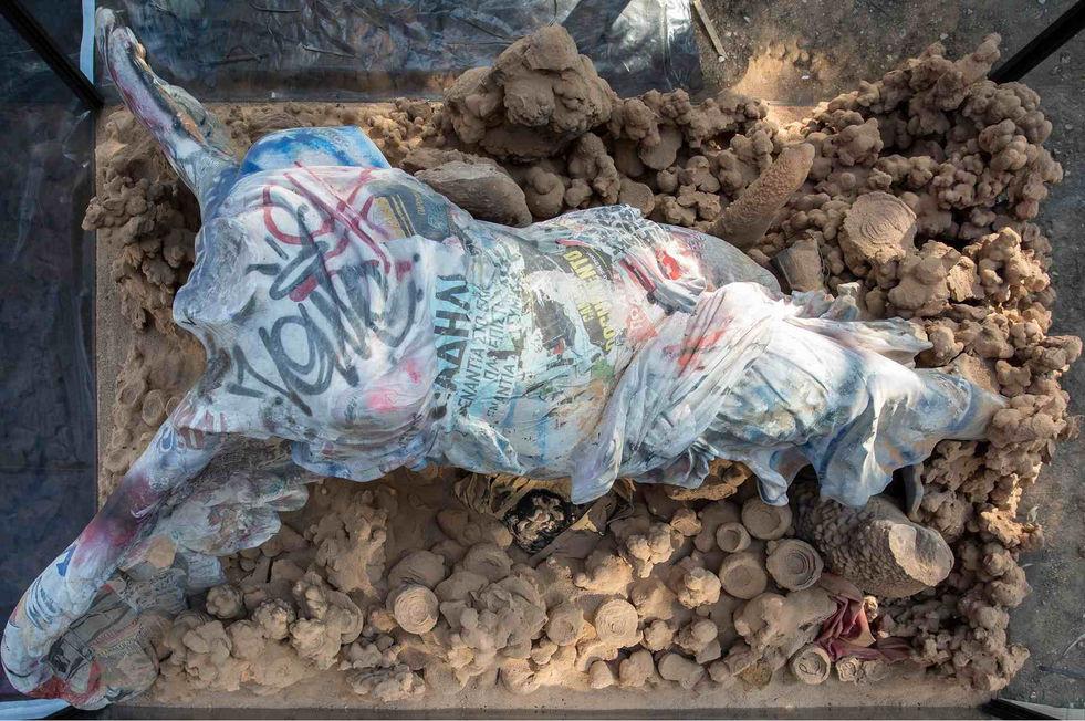 Réplique de la Victoire de Samothrace avec des graffitis et des affiches de rue collées, sac à dos, t-shirt, drapeau chinois, stromatolithes et sol natif.